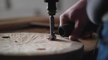 carpinteiro perfura uma prancha de madeira com uma fresa de madeira