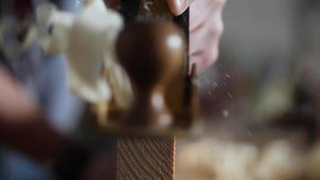 carpinteiro aplaina uma prancha de madeira com uma plaina manual