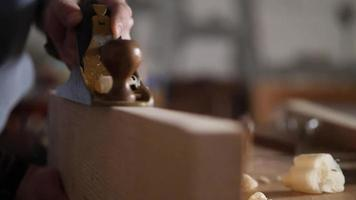 woodworker planes a wooden plank with a hand planer video