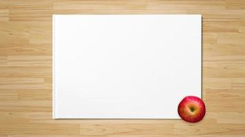 Red apple on white paper on wooden background