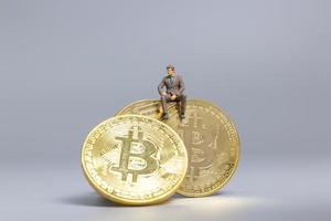 Miniature businessman sitting on Bitcoin coins, future investment concept