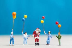 Papá Noel en miniatura y niños sosteniendo globos, feliz navidad y feliz año nuevo concepto