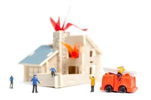 Bomberos en miniatura cuidando de una emergencia de incendio en una casa de madera foto