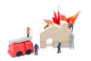 Bomberos en miniatura cuidando de una emergencia de incendio en una casa de madera