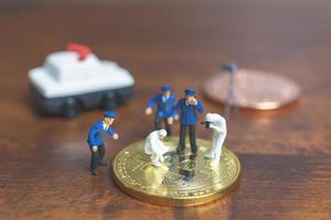 Policía y detectives en miniatura de pie delante de la criptomoneda bitcoin, concepto de ciberdelincuencia