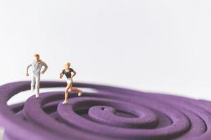 Pareja en miniatura corriendo sobre un campo circular púrpura