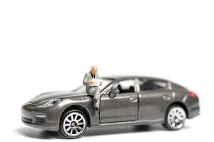 Miniature people sitting on a car on a white background photo