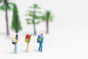 Miniature travelers with backpacks walking on a white background, travel and adventure concept photo