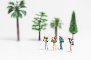 Viajeros en miniatura con mochilas caminando sobre un fondo blanco, concepto de viaje y aventura