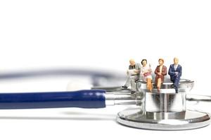 Miniature people sitting on a stethoscope on a white background, health care concept