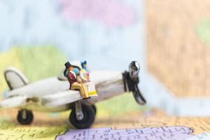 Gente en miniatura sentada en un avión con un fondo de mapa del mundo, concepto de viaje