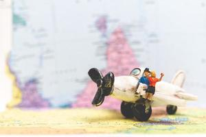 Miniature people sitting on an airplane with a world map background, travel concept