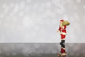 santa claus en miniatura con una bolsa sobre un fondo bokeh, feliz navidad y feliz año nuevo concepto.