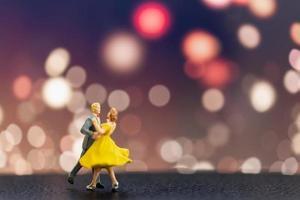 Pareja en miniatura bailando con un fondo bokeh, concepto de día de San Valentín