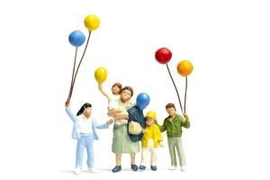 Miniature children holding balloons with a parent isolated on a white background