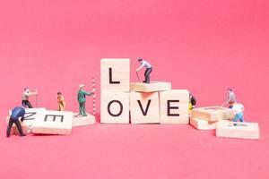 Trabajador en miniatura que se une para construir la palabra amor en bloques de madera con un fondo rosa, concepto del día de San Valentín foto