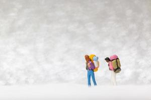 Miniature backpackers walking on a snow background, winter concept photo