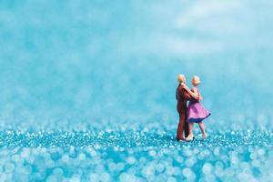 Pareja en miniatura bailando sobre fondo azul brillo, concepto de día de San Valentín