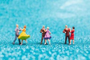 Parejas en miniatura bailando sobre fondo azul brillo, concepto de día de San Valentín