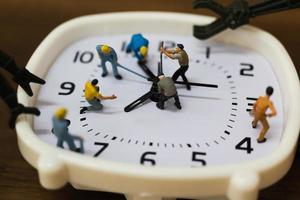 Miniature team working on an alarm clock, working time concept