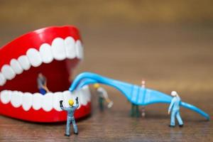 Miniature workers repairing a tooth, healthcare and medical concept photo