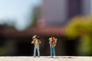 Miniature travelers with backpacks standing on a road, travel concept photo