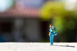 Miniature traveler with a backpack standing on a road, travel concept photo