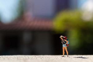 Viajero en miniatura con una mochila de pie en una carretera, concepto de viaje foto