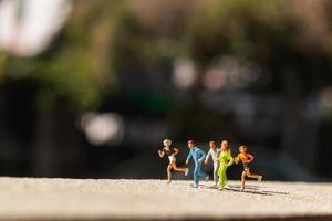 Grupo en miniatura de personas corriendo en una carretera de hormigón, concepto de estilo de vida saludable