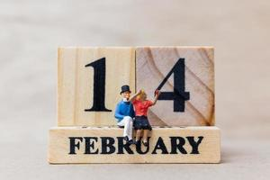 Miniature couple with wooden blocks 14 February text on a wooden background, Happy Valentine's Day concept photo