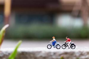 Viajeros en miniatura con bicicletas en el parque, concepto de estilo de vida saludable foto