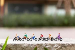 Miniature travelers with bicycles in the park, healthy lifestyle concept