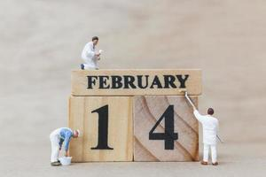 Miniature people painting wooden blocks with 14 February on a wooden background, Happy Valentine's Day concept photo