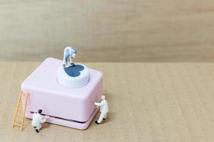 Miniature people painting a heart-shaped punching machine, Valentine's Day concept photo