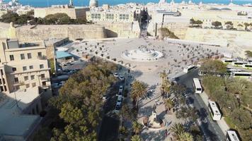 a fonte de tritão do lado de fora do portão da cidade de valletta, malta. frente aérea video