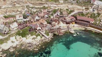 Popeye Village Fun Park e águas turquesa do Mediterrâneo na baía Anchor, em Malta - foto aérea panorâmica video