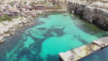 Toma aérea de ángulo bajo sobre el muelle en Anchor Bay, mostrando Popeye Village rodeado por el mar mediterráneo turquesa en Malta video