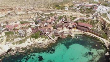 estabelecendo uma foto aérea de arco do mar turquesa banhando uma costa mediterrânea na baía de âncora, com a vila de Popeye contra a colina na ilha de Malta video