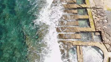 Imagens de 4k de uma vista aérea dos banhos de sliema em malta - piscinas esculpidas nas rochas da costa em sliema video