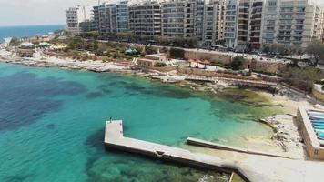 Pier over the warm Mediterranean sea on Sliema's seaside, in Malta - Slow Orbit aerial shot video