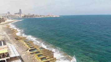 Sliema rocky seascape blocked by Promenade and city skyline, in Malta - Revealing Pan aerial video