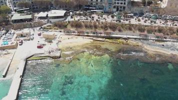 um retrocesso revela imagens aéreas de drones 4k de uma praia da cidade turística de sliema, malta, vista da costa do oceano mediterrâneo. video