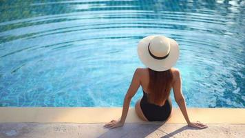Woman sit back around pool on vacation