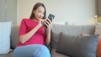 Woman use mobile phone on sofa in bedroom