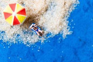 Miniature people sunbathing on a beach, summertime concept photo