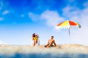 Gente en miniatura tomando el sol en una playa, concepto de verano foto