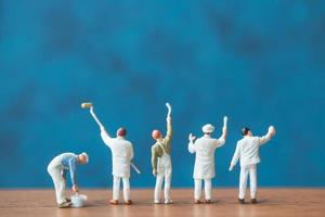Miniature people holding brushes in front of a blue wall background