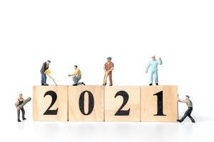 Trabajadores en miniatura que se unen para crear bloques de madera con el número 2021, concepto feliz año nuevo foto