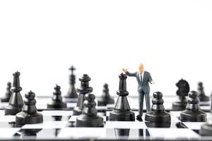 Empresario en miniatura de pie sobre un tablero de ajedrez, concepto empresarial y de competencia foto