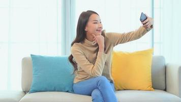Young asian woman uses mobile phone on sofa